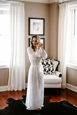 Bride with curled wedding hair in bridal suite black cowhide rug white long sleeve sheer robe gown