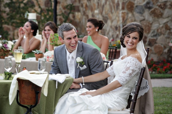 Bride and groom at sweetheart table laugh with guests
