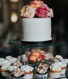 mini wedding cake with cupcakes displayed
