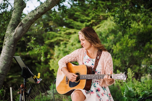 Woman in sun dress playing guitar at outdoor ceremony