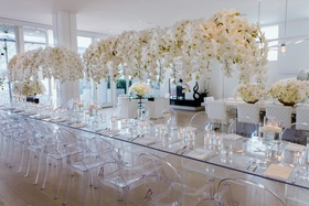 Opulent arrangements of orchids float above a collection of lucite chairs and tables.