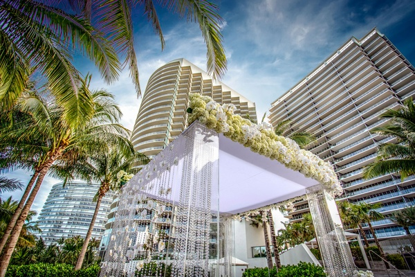lucite chuppah in florida surrounded by palm trees, florida destination wedding