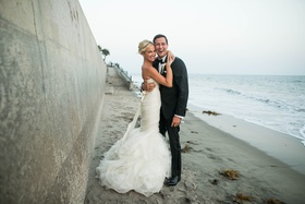 bride in gemma vera vang gown hugging groom in tux in front of wall on beach in santa barbara
