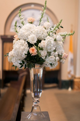 Bouquet of white hydrangeas, roses, snapdragons, and light orange roses in a tall glass vase