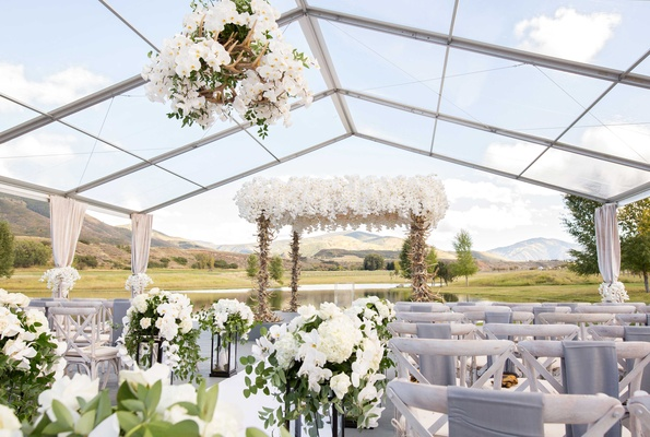 Clear wedding tent on Aspen ranch with antler orchid flower chandelier and wood chairs