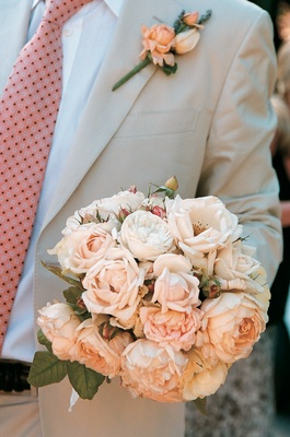 Groom holds bouquet with peach and white peonies