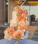 White three layer wedding cake with fresh orange and white rose flowers, rhinestone monogram topper
