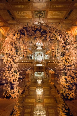 Mirror aisle runner with flower arches and tiled ceiling at The Plaza Hotel with chandeliers flowers