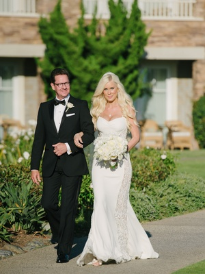 Bride in a thin strapped Galia Lahav dress with lace panels, white bouquet, and father in a black