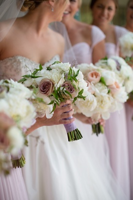 Bridesmaid bouquet of white peonies, purple roses, and greenery hand-tied in light purple ribbon