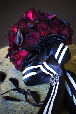 Bride's bouquet of black baccara roses and magenta calla lilies wrapped in black and white ribbon