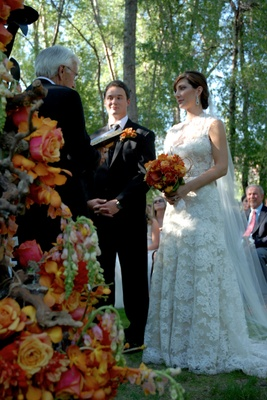 Bride in a lace Monique Lhuillier gown and groom in a black tuxedo with officiant