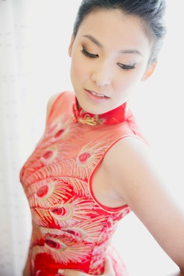 bride in red and gold peacock feather print qipao for tea ceremony