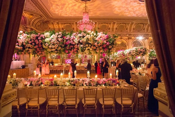 Wedding reception with long table low runner of flowers with candles and tall centerpieces pink