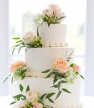 Three layer white wedding cake with pastel orange roses, green hydrangea sprigs, and greenery