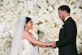 manny smith interscope wedding, bride and groom hold hands, kim and kanye inspired floral wall