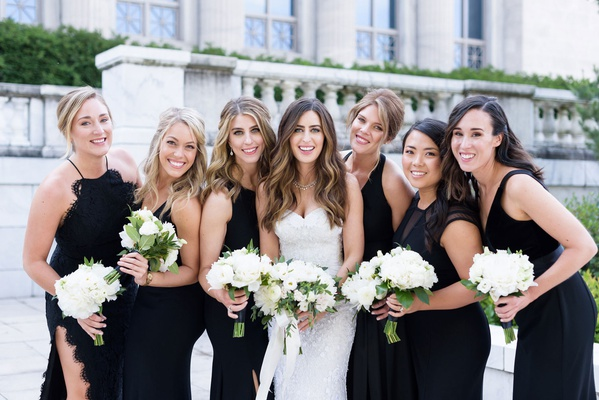 wedding photo of bride with bridesmaids mismatch black dresses white bouquets greenery ribbon