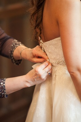 a bride gets helps getting zipped into her wedding gown before her church ceremony