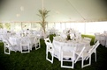 Party tent filled with lanterns and round tables