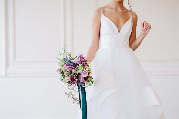unique bridal bouquet with blue and purple tied with forest green ribbon