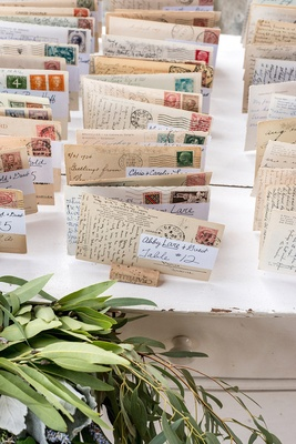 Rustic tented reception with Italian postcards used as place cards on wine corks, white dresser