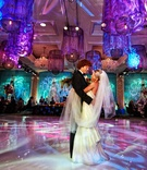 bride in anne barge holds veil during first dance on vibrant dance floor