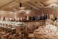 wedding reception ballroom long table round tables greenery white flowers gold chairs chandelier