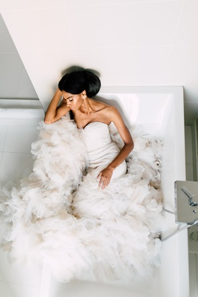inbal dror fluffy mermaid gown, african american model posed in bathtub with train spilling out