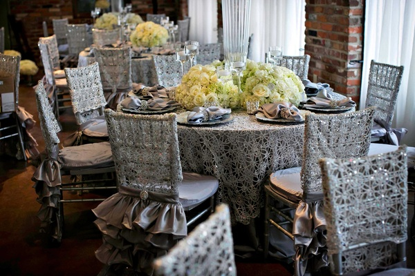 Silver table linens and ruffle chair covers with low ivory flower centerpieces