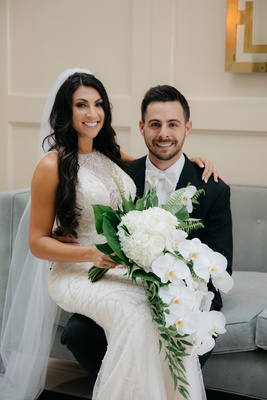 bride in maggie sottero beaded embroidered gown sitting on lap of groom with white bow tie