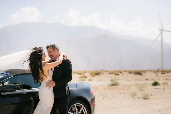 Bride in Galia Lahav wedding dress and groom in tuxedo by wind mills and Aston Martin car desert