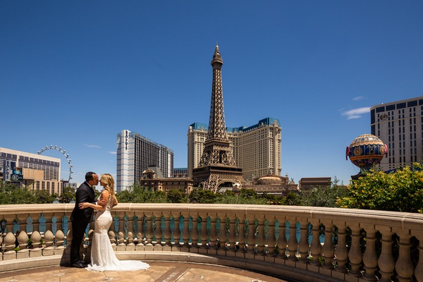 bride and groom on balcony of bellagio with view of the las vegas strip eiffel tower