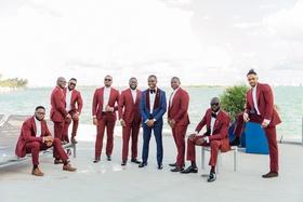 groom in navy tuxedo with burgundy  lapels, groomsmen in maroon suits