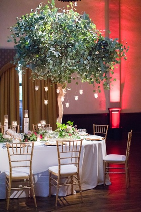 Tree as wedding reception centerpiece with hanging candles, chiavari chairs