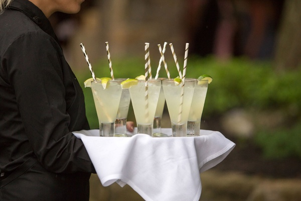 Server carrying white tray with signature cocktail drinks stripe straw lime garnish margaritas