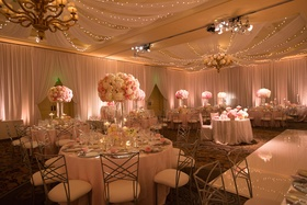 Ballroom reception with twinkle lights draping and tall flower arrangements