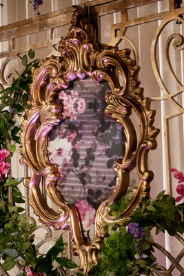 ornate gold frame displaying floral fabric