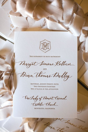 cream invitation with gold lettering and monogram for catholic ceremony