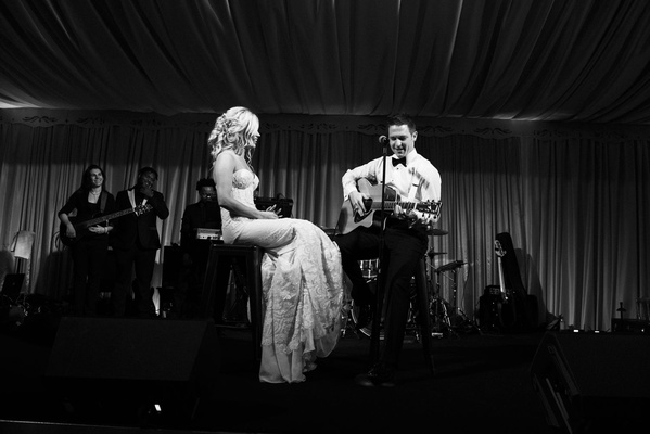 Black and white photo of bride and groom on stage for surprise song written by groom to bride