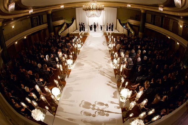 Long white aisle runner lined with candelabra candles chandelier oval drapery chuppah and guests