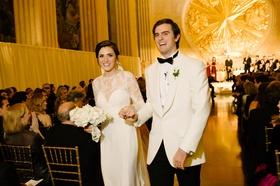 Bride in white illusion lace long sleeve dress groom in white tuxedo jacket gold backdrop texas nye