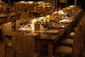 Wood farm table at wedding reception with lace chair covers
