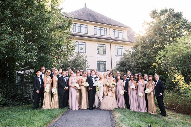 Bride and groom with groomsmen in tuxes and bridesmaids in gold and pink dresses flower girl