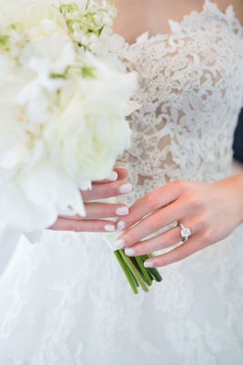 Bride with pretty manicure holding white bouquet emerald cut diamond engagement ring side stones