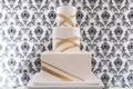 three tier wedding cake with glassy finish and modern gold stripes