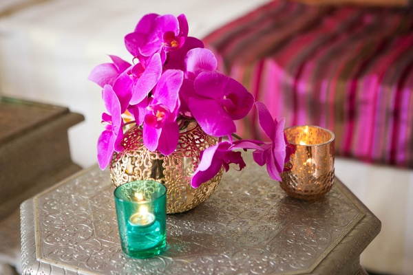 Moroccan-themed engagement party silver table with golden vase, hot pink orchids, votive candles