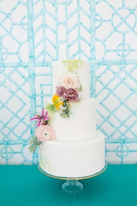 White fondant wedding cake three layer cascading fresh flowers yellow purple pink green paint