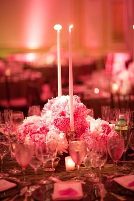 Low floral arrangement surrounding candlesticks