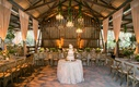 Naked cake in center of barn open side venue with drapery chandeliers wood beams wood chairs long