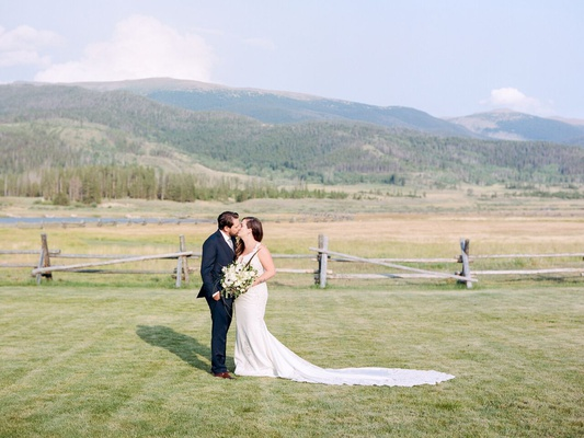 bride in pnina tornai wedding dress with lace cutouts and inserts kisses groom in field